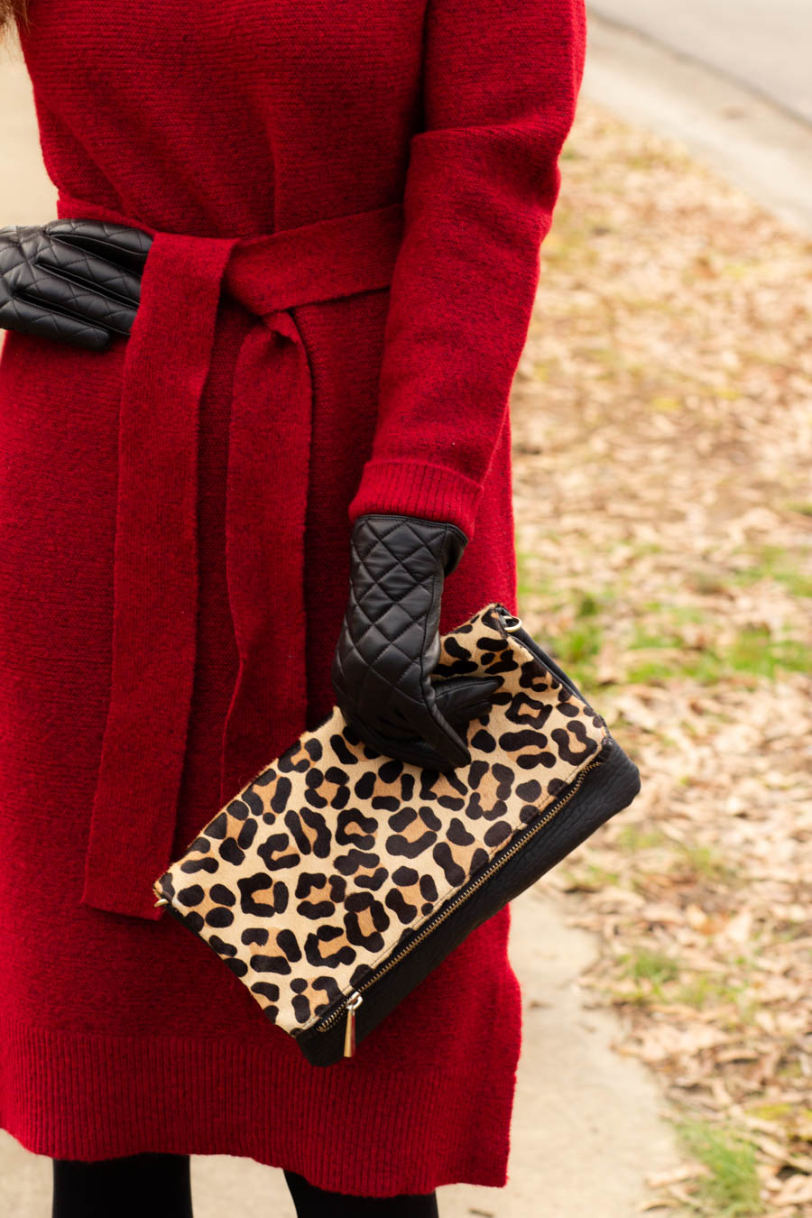 Women's red sweater dress with leopard clutch