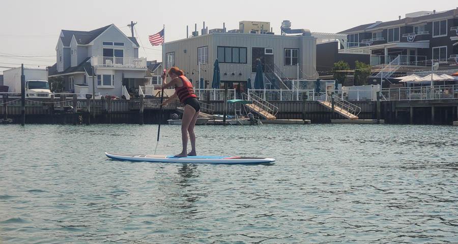 Lady paddleboarding on bay