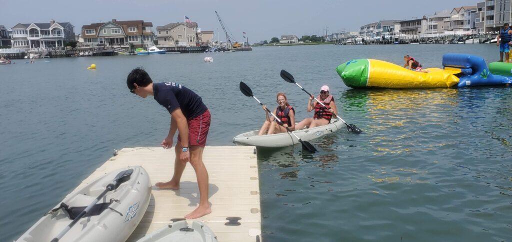 Two women kayaking in bay