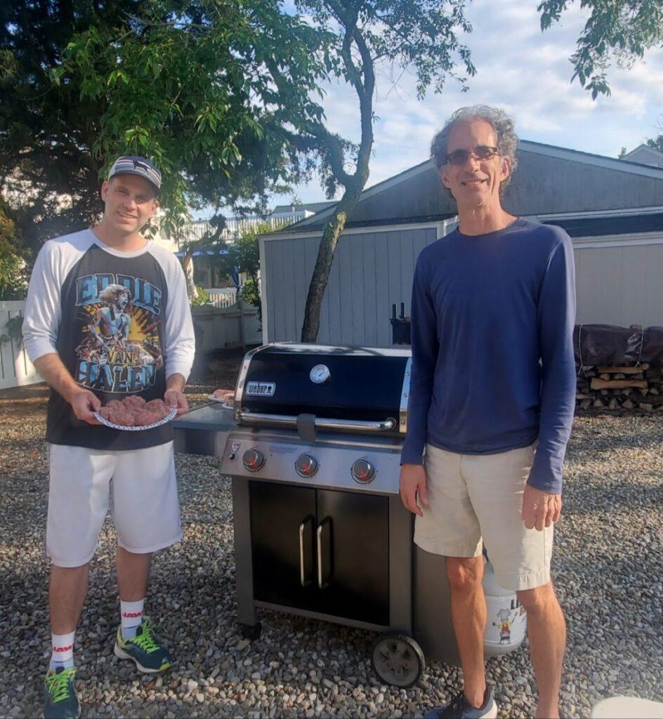 Two men grilling in backyard