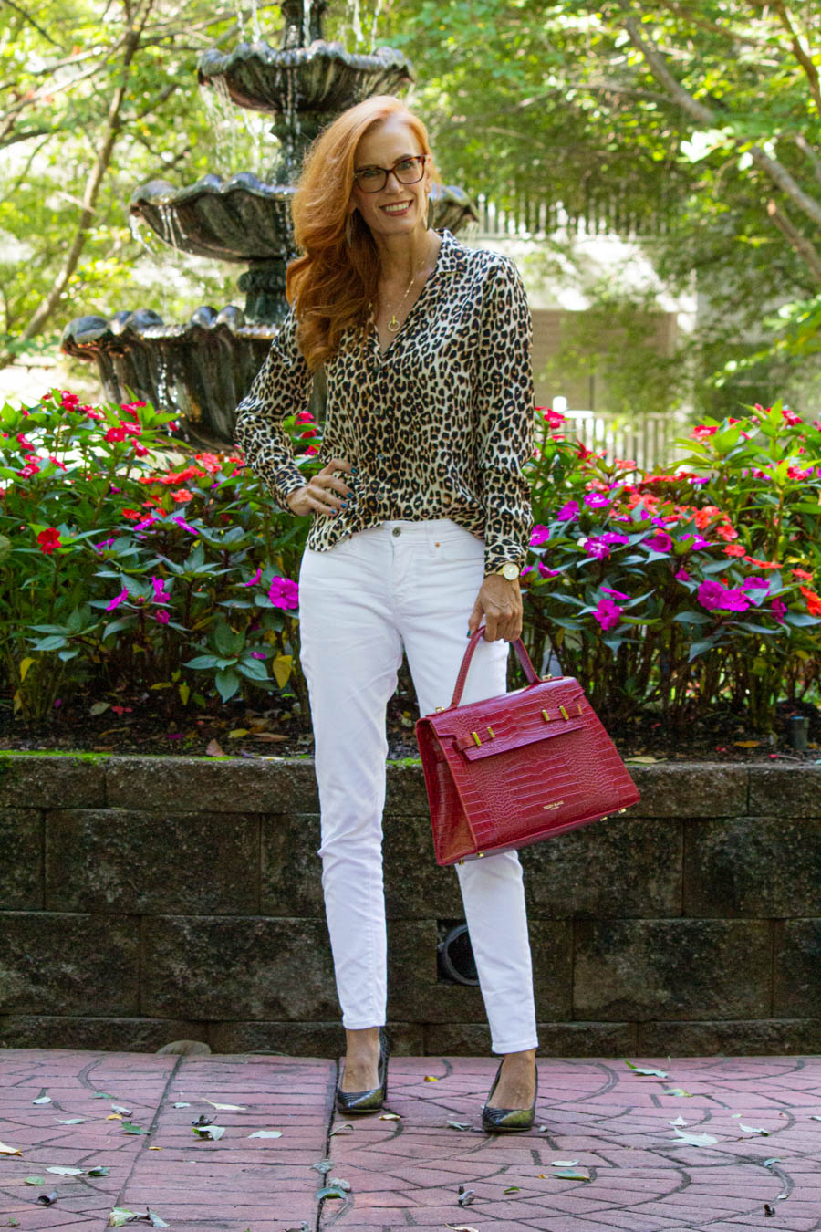 leopard blouse with white denim and red bag